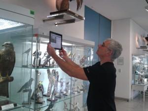 Der akademische Leiter Stefan Heyl aktiviert über eine Kodierung an der Vitrine mit dem iPad verschiedene Vogelstimmen
