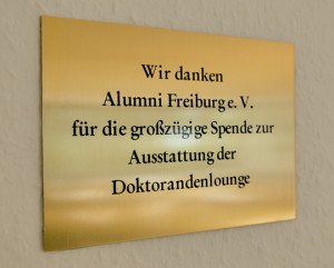 A brass plaque in the doctoral candidate lounge acknowledges the support provided by alumni. The plaque was mounted as part of a small celebration in October.
