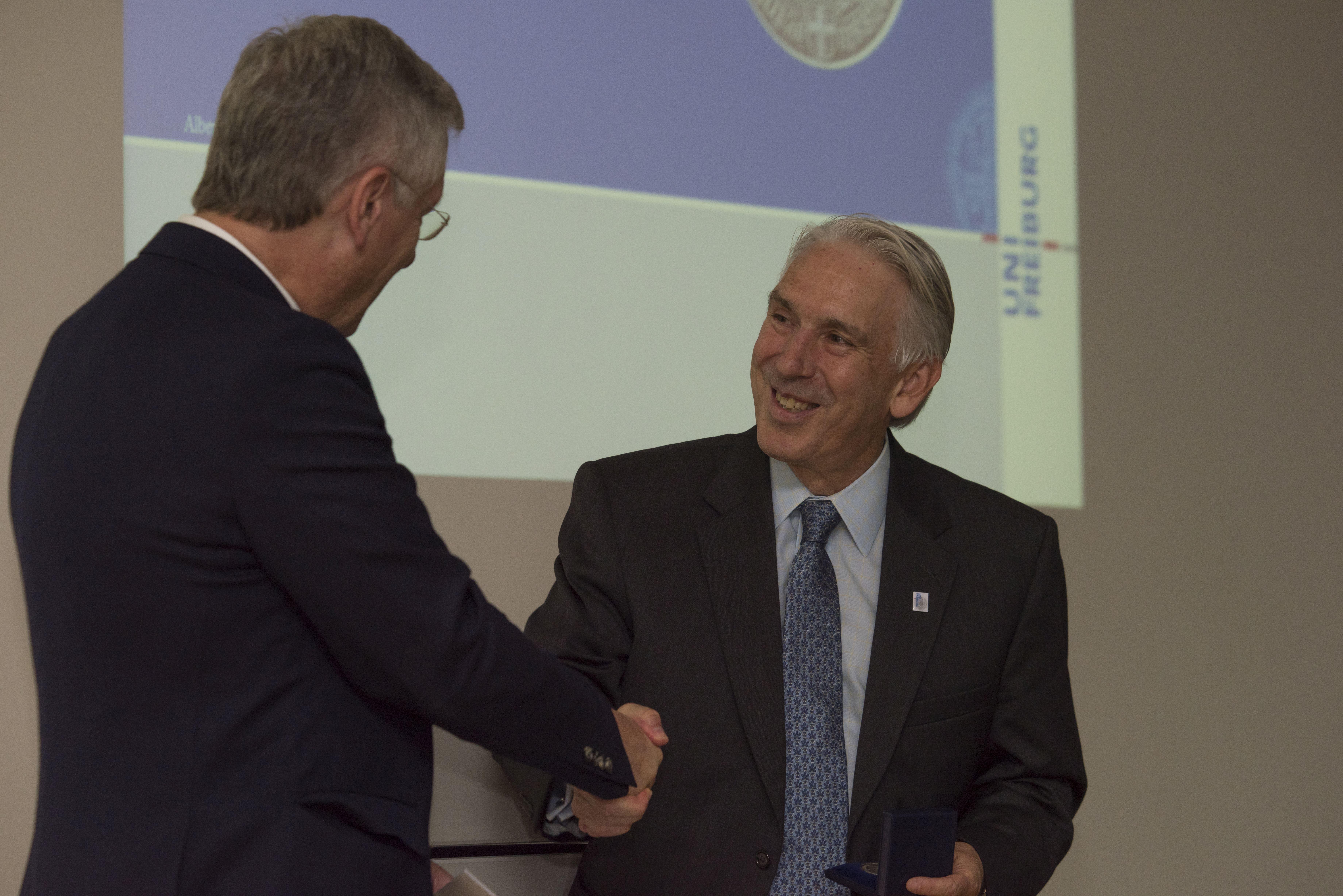 Rektor Schiewer überreicht Jeffrey Himmel die Universitätsmedaille
