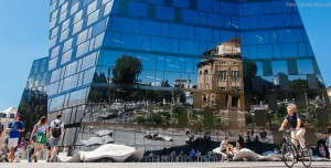 Viewed from north the Freiburg Opera House is mirrored in the glass front of the new University Library. Photo: Sandra Meyndt